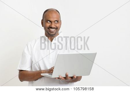 Portrait of mature casual business Indian man using laptop computer, looking side and smiling, standing on plain background with shadow.