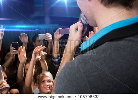 holidays, music, nightlife and people concept - close up of singer singing on stage over happy people crowd taking picture by smartphones and waving hands at concert in night club