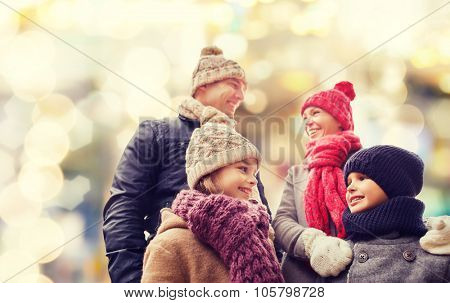 family, childhood, season, holidays and people concept - happy family in winter clothes over lights background