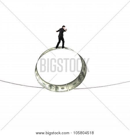 Businessman Standing On Roll Of Dollar Bills Balancing Tightrope