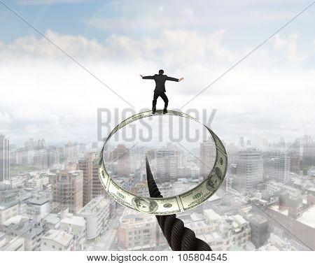 Businessman Standing On Roll Of Dollar Bills Balancing Wire