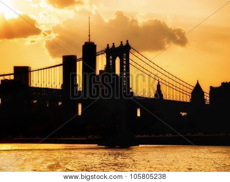 Silhouette of the downtown Manhattan skyline and the Manhattan Bridge at sunset with reflections on the water