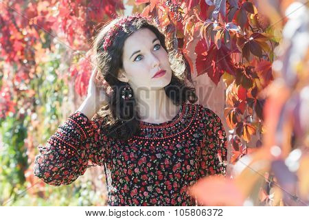 Portrait of daydreaming autumn girl with autumn wreath at red floral background of grape woodbine