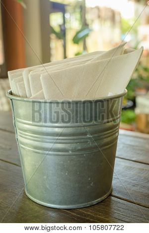 Tissue Paper In Bucket On Wooden Table
