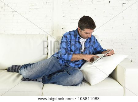 Young Attractive 30S Man Using Digital Tablet Pad Lying On Couch At Home Networking Looking Relaxed