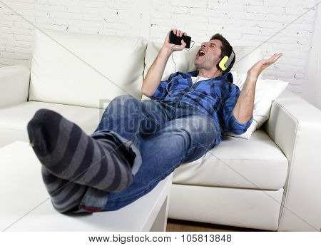 Happy Crazy Man On Couch Listening To Music Holding Mobile Phone As Microphone