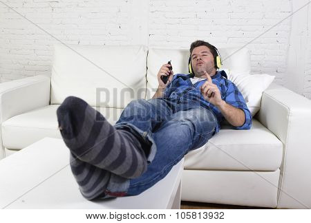 Young Attractive Man Having Fun Alone Lying On Couch Listening To Music With Mobile Phone And Headph