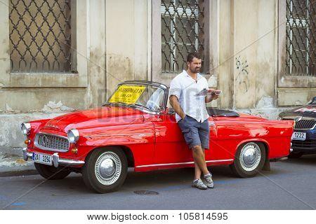A Man Stands At A Bright Red Retro Car Skoda