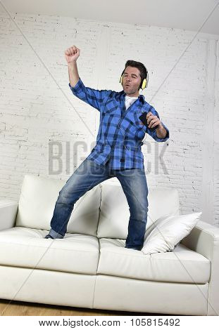 20S Or 30S Man Jumped On Couch Listening To Music On Mobile Phone With Headphones Playing Air Guitar