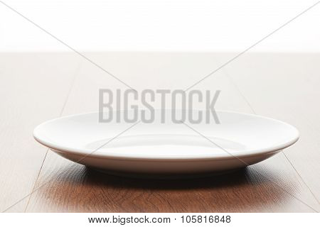 Empty white ceramic plate on bright light brown wooden table