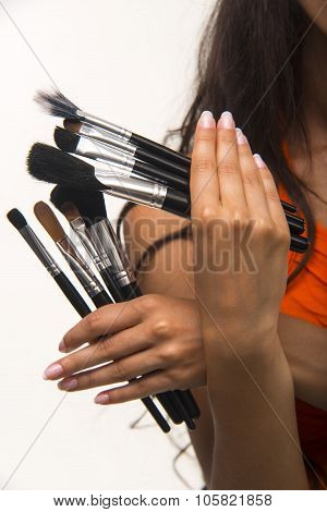 Glamour lady is showing cosmetic brush set close