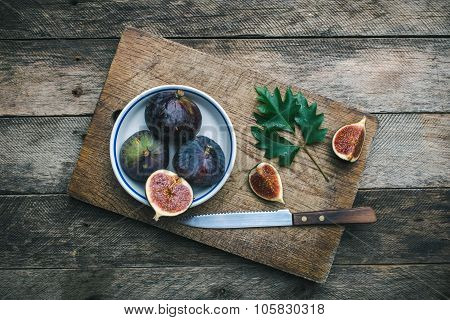 Figs And Knife On Chopping Board And Wooden Table