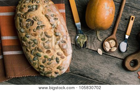 Pumpkin With Bread And Seeds On Rustic Wood