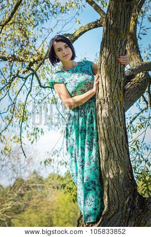 beautiful girl in a long dress next to a tree on a sunny day