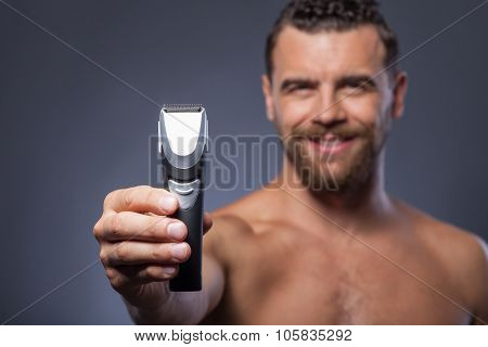 Cheerful bearded guy is showing new shaver