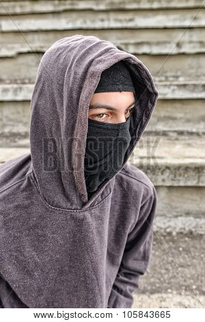 Unrecognizable Young Man Wearing Black Balaclava Sitting On Old Stairs