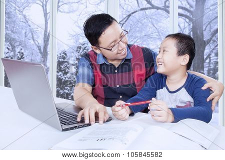 Young Father Talking With His Son While Studying