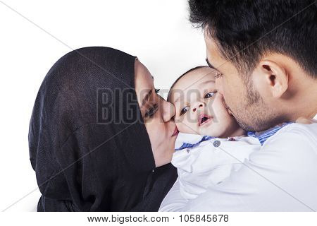 Young Man And His Wife Kissing Their Baby