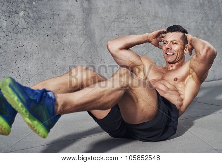 Muscular Male Fitness Athlete Doing Sit Ups While Smiling