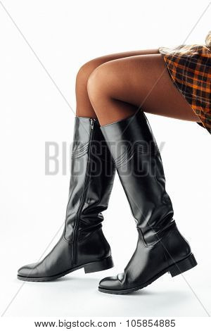 woman legs wearing black leather high boots, isolated on white
