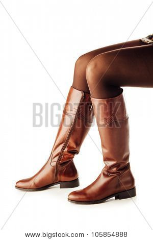 woman legs wearing brown leather high boots on white background