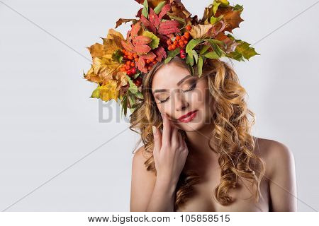 portraiture style fashion beautiful sexy girl with red hair fall with a wreath of colored leaves