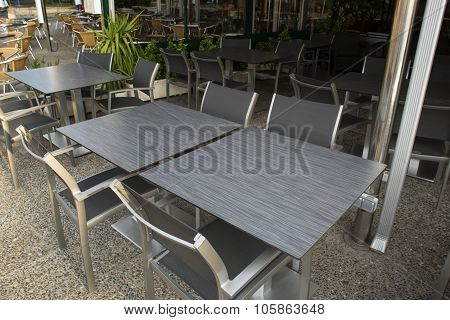 Metal And Dark Gray Stone Tables And Chairs Outdoor Of Restaurant.