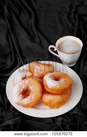 donuts with powdered sugar and coffee on a black background drapery fabric