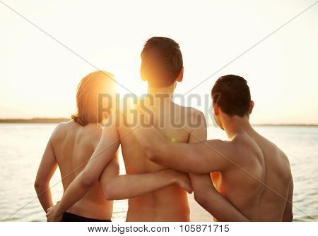 Three Young Teenage Boys Watch The Sunset
