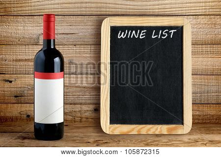 Wine Bottle And Blackboard For Wine List On Wooden Background