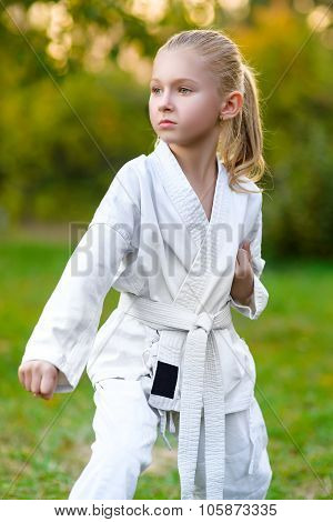 girl in white kimono during training karate exercises at summer outdoors
