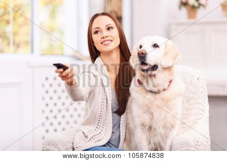 Young girl showing something to her dog on TV.