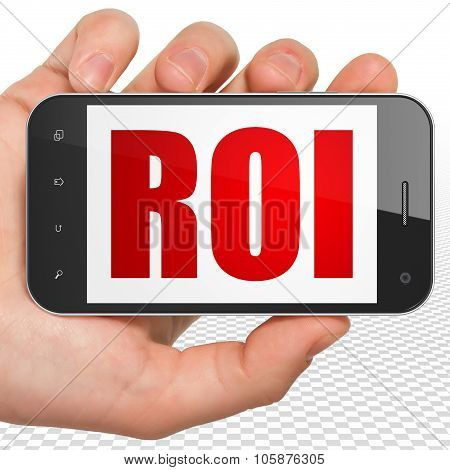Finance concept: Hand Holding Smartphone with ROI on display