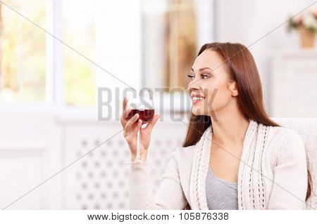 Appealing young lady enjoying a glass of vine.