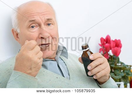 Elderly gentleman takes in his cough syrup.