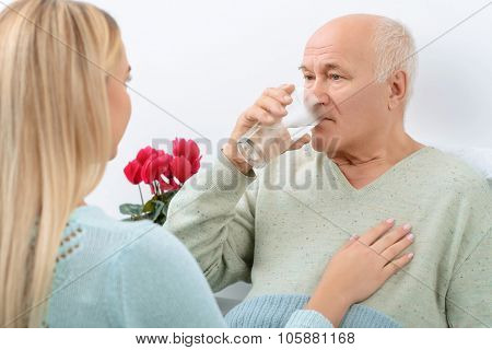 Elderly man drinks water given by granddaughter.