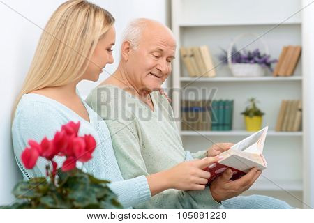 Two relatives looking through family album.