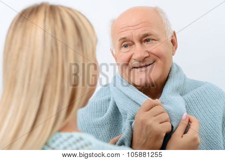 Smiling aged man is being wrapped in blanket.