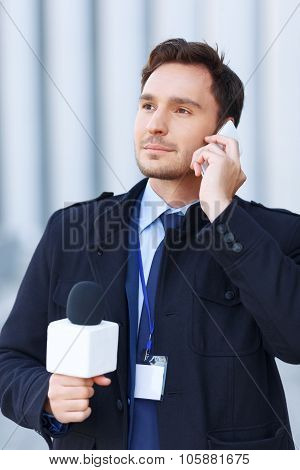 Smart-looking man is talking over the phone.