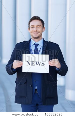 Smiling journalist holds a sheet of paper.