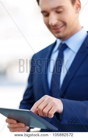 Smiling gentleman in the process of using a tablet.