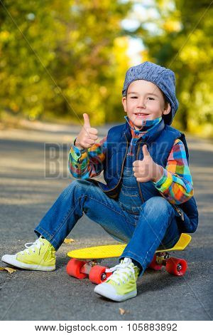 Smiling boy sitting on color plastic penny board skateboard and showing thumbs up at park