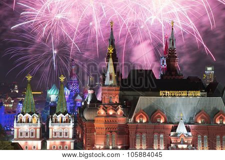 Fireworks explode over Kremlin, St. Basil Cathedral at night on Red Square in Moscow. Text on building: historic museum