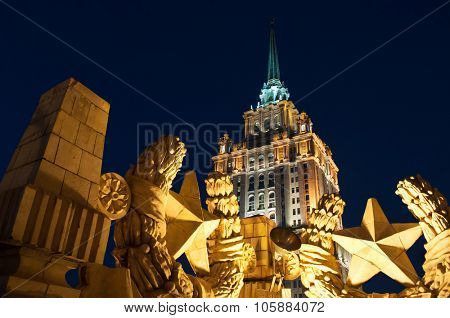 Tower with spire on Ukraine hotel (Stalin skyscraper) and concrete soviet stars at night in Moscow