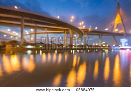 Abstract blurred bokeh water reflection city highway light with suspension bridge
