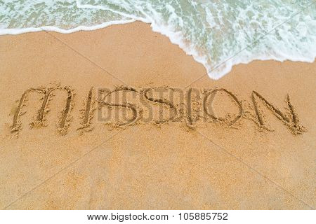 Mission Inscription Written On Sandy Beach With Wave Approaching