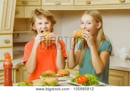 smiling happy boy and girl eating hamburgers or sandwiches