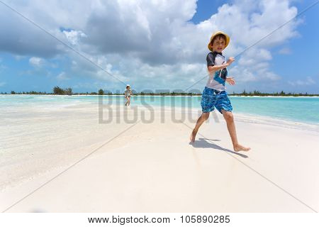 Stylish boy running on a tropical beach