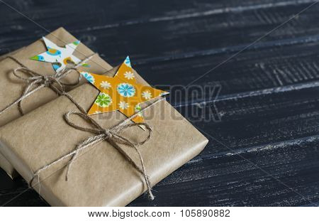 Christmas Gifts In Kraft Paper With A Homemade Tag On A Dark Wooden Surface. Vintage And Rustic Styl