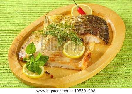 roasted carp fillets with lemon slices, dill, basil and chili pepper on wooden cutting board and green place mat